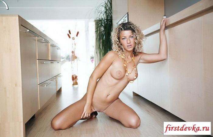 Кудрявая девчонка позирует у себя на кухне