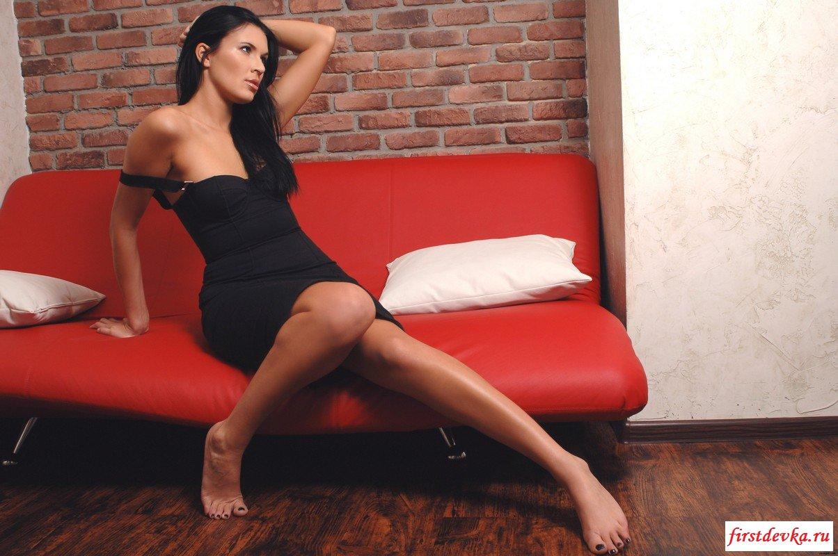 Скромная брюнетка на красном диване.