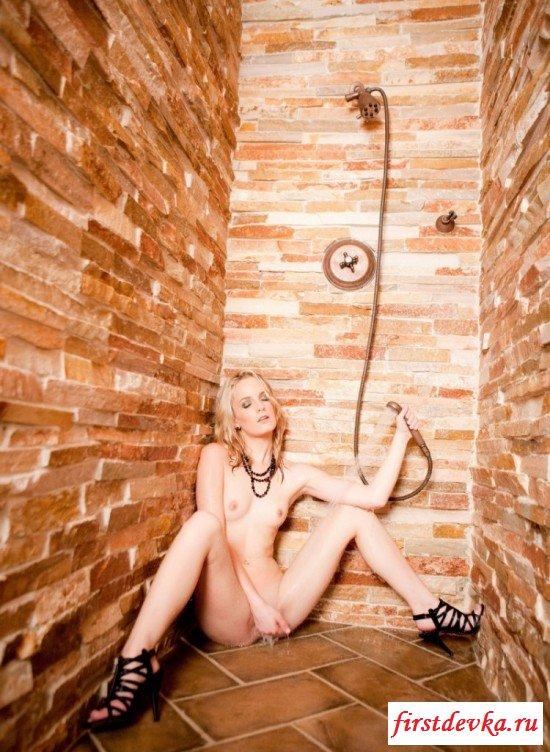Стройная блондинка в платье купается в душе